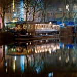 Glassboat - a floating boat restaurant on the water in Bristol. Reflection of boat in the water at night