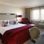 Deluxe Room showing bed with red bedspread, floral pillows and desk