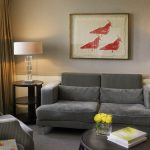Suite Lounge with grey sofa, coffee table with yellow flowers and a book and picture of three red birds on the wall