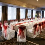 William Jessop room at the Bristol Hotel set up for a wedding with long table and red table runner and matching red bows on the chairs