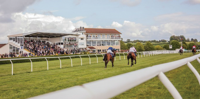 Wincanton Racecourse: four horses running down a track while people watch in the stands