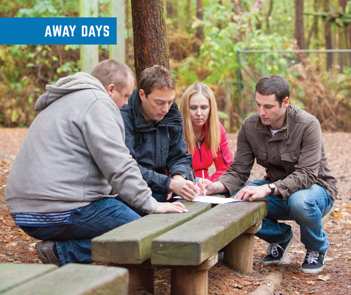 Corporate retreats: four people in a forest setting on a bench looking at a map