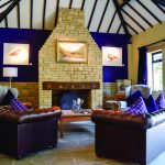Lady's Wood stone lodge with comfy brown leather armchairs in front of the fire