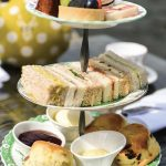 afternoon tea stand with cake and sandwiches