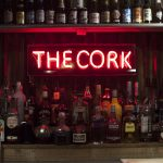 Red neon sign of The Cork above a variety of bottles on the bar